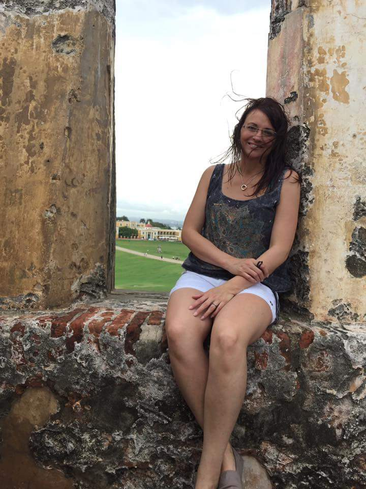 Marcy sitting in an overlook at Castillo San Felipe del Morro, Puerto Rico